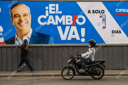Men with masks are seen as they pass near a billboard of the presidential candidate Luis Abinader, in Santo Domingo, Dominican Republic, 04 July 2020. Dominicans go to the polls on 05 July to choose the successor to President Danilo Medina, in office since 2012, amid the current coronavirus pandemic, whose cases have increased in recent weeks, which could increase abstention.