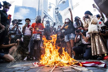 Protesters burn U.S. flags during a protest near Trump International Hotel, in New York