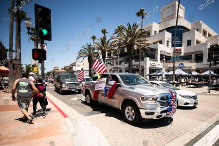 A woman holds a placard reading 'Recall Newsom Free California' in a pickup truck displaying American flags for the 4th of July amid the coronavirus pandemic in Huntington Beach, California, 04 July 2020. California Governor Gavin Newsom and Orange County authorities have ordered the beaches to be close on the Fourth of July as the number of people infected by the virus have spiked in California and in the County.