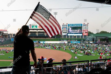 A fan waves an American flag while county music artist Granger Smith headlines a special socially distanced concert and fireworks event
