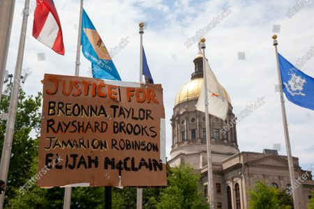 A protester holds up a sign in front of the Georgia state capitol in downtown Atlanta with signs during a July 4th protest for the Black Lives Matter movement.
