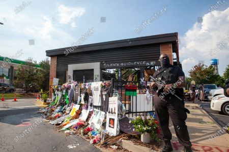 Armed men guard the memorial at the Wendys where Rayshard Brooks was killed by police.