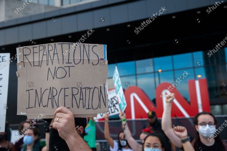 Protesters hold signs during a protest on July 4th for reparations and in support of Black Lives Matter in front of the CNN center in Atlanta.