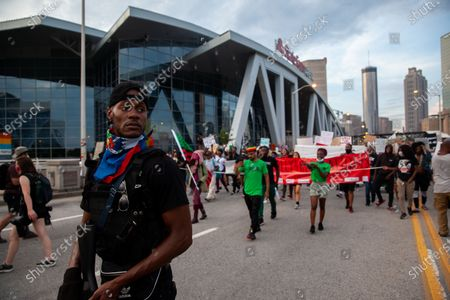 """A member of the """"Black Revolutionaries,"""" a self described communitty defense group, walk along protesters while armed in front of the State Farm arena in downtown Atlanta."""