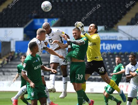 Andre Ayew of Swansea City competes in the air with Connor Wickham and Joe Wildsmith of Sheffield Wednesday.