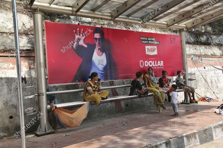 Stock Picture of Street vendor women with their children take rest at a bus waiting shelter on a hot afternoon in Jammu, India, . A commercial hoarding featuring Bollywood star Akshay Kumar is behind