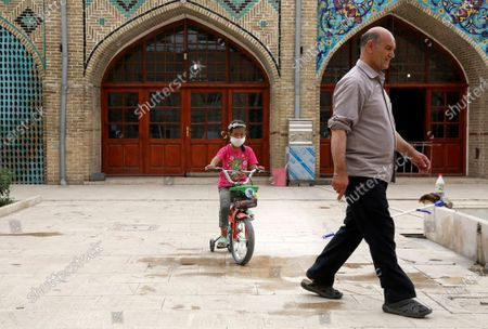 Girl wearing a protective face mask to help prevent the spread of the coronavirus rides her bicycle in the courtyard of a mosque, in the city of Zanjan, some 330 kilometers (205 miles) west of the capital Tehran, Iran, . Iran on Sunday instituted mandatory mask-wearing as fears mount over newly spiking reported deaths from the coronavirus, even as its public increasingly shrugs off the danger of the COVID-19 illness it causes