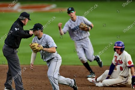 Coastal Carolina's Cory Wood, left, and Scott McKeon, center, react after tagging Clemson's Logan Davidson, right, out at second base during an NCAA college baseball game, in Clemson, S.C. Coastal Carolina already had a small athletic budget, and that was before a 15% spending cut was ordered because of projected declines in state funding and student fees stemming from the coronavirus pandemic. The school's 19-sport program includes about 450 athletes, and with individual tests currently costing about $100, testing could cost hundreds of thousands of dollars by the end of the 2020-21 academic year