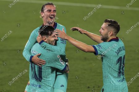 Barcelona's Antoine Griezmann, top, is congratulated by teammate Lionel Messi, left, and Jordi Alba, right, after scoring his side third goal during the Spanish La Liga soccer match between FC Barcelona and Villareal at La Ceramica stadium in Villareal, Spain