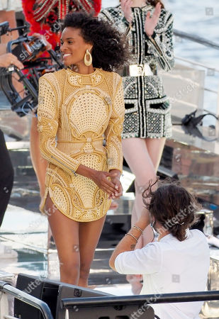 """Model Cindy Bruna wears golden large earrings, a golden knitted dress with embroidery and geometric patterns during the """"Balmain"""" sur seine"""" Fashion show that was held on a """"peniche"""" Parisian boat on the seine river to celebrate the 75th anniversary of the brand during the Couture Paris fashion week on July 05, 2020 in Paris, France."""