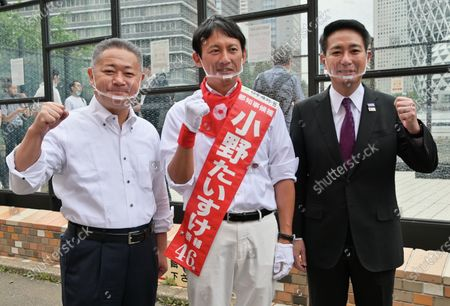 (L-R)Secretary General of Restoration Party, Nobuyuki Baba , candidate Taisuke Ono and Member of the House of Representatives Seiji Maehara attend the campaign speeches for the Tokyo gubernatorial election near Shinjuku station in Tokyo, Japan.