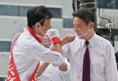 Stock Photo of Candidate Taisuke Ono(L) elbow bumps with Member of the House of Representatives Seiji Maehara attend the campaign speeches for the Tokyo gubernatorial election near Shinjuku station in Tokyo, Japan.