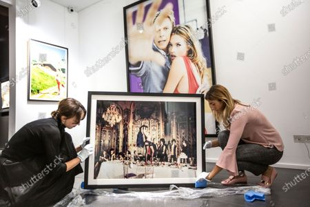 curators unwrapping 'Baccarat, Paris, 2007' with the photographs  'Hidi, Kitzbuhei, 2003' next to 'Kate and David, New York, 2003' hung on the gallery wall in the background.