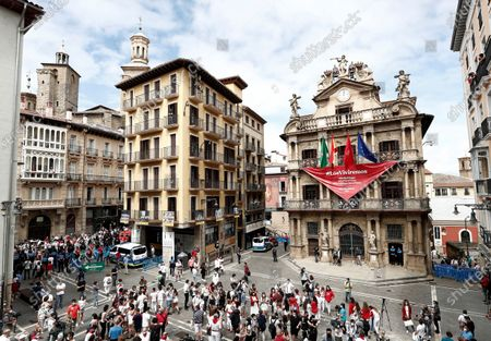 Stock Image of People, many of them wearing the traditional white-and-red San Fermin attire, gather around noon in front of City Hall - from which hangs a giant banner in the shape of the San Fermin festival's emblematic red kerchiefs, promising 'We Will Experience Them' - in Pamplona, northern Spain, 06 July 2020. Pamplona's idiosyncratic Running of the Bulls, known as the Sanfermines, would have normally kicked off on 06 July with the 'Txupinazo' (an opening ceremony involving the firing of a pyrotechnic rocket from City Hall's main balcony). However, the bull-running festival made world-famous by Ernest Hemingway in his 1926 novel 'The Sun Also Rises' has been canceled this year due to the ongoing pandemic of the COVID-19 disease caused by the SARS-CoV-2 coronavirus.