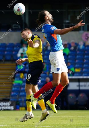 Stock Image of Christian Burgess of Portsmouth wins a header over Jamie Mackie of Oxford United