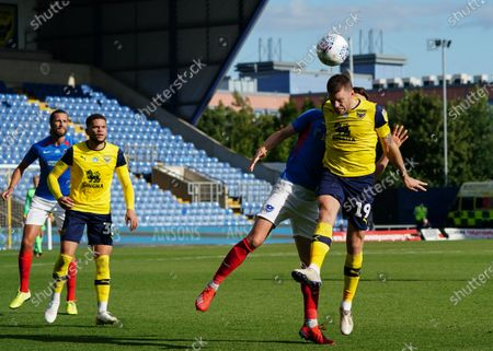 Jamie Mackie of Oxford United wins a header over James Bolton of Portsmouth