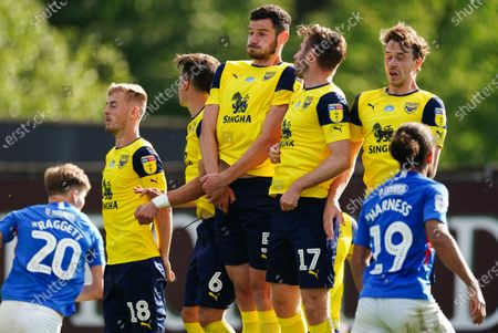 Elliott Moore of Oxford United and James Henry of Oxford United jump to defend a free-kick