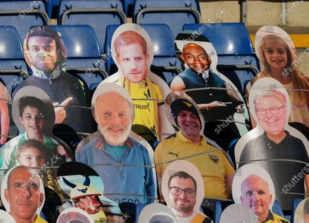 A cardboard cutout of Prince Harry sits in the stands alongside the Oxford United fans