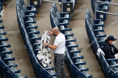 New York Yankees general manager Brian Cashman spreads towels out before sitting down to watch the Yankees play an intrasquad baseball game, at Yankee Stadium in New York