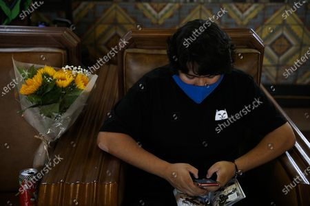 Miguel Gomez, 20, waits for a train next to his flowers at Union Station in Los Angeles, . The coronavirus is blamed for over a half-million deaths worldwide, including more than 130,000 in the U.S., according to the tally kept by Johns Hopkins University