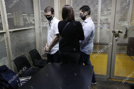 The sons of former Panamenian President Ricardo Martinelli, Ricardo Martnelli Linares, right, and his brother Luis Enrique Martinelli Linares, left, are accompanied by one of their lawyers before a hearing at a holding cell of the judicial court building in Guatemala City, . Guatemalan police detained the Martinelli brothers on an Interpol warrant for money laundering, as they attempted to board a private plane out of the country