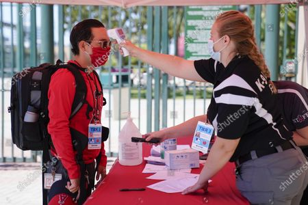 Stock Photo of Ricardo Zapata, left, a photographer for the Los Angeles Angels, has his temperature taken by Sarah Morris before entering Angels Stadium for baseball practice, in Anaheim, Calif. New protocols like temperature checks, social distancing, and limiting amount of people allowed in sports venues have been put in place due to the spread of COVID-19
