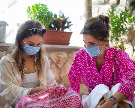 Stock Picture of HRH Princess Iman bint Abdullah and HRH Queen Rania with face masks, in scarf embroidery class