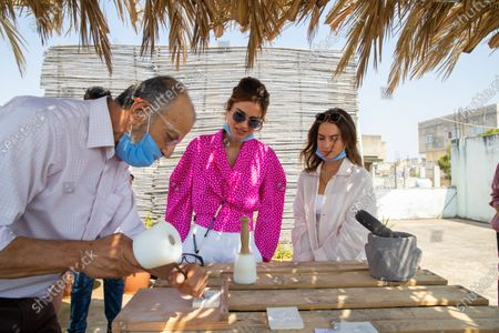 Queen Rania, with HRH Princess Iman bint Abdullah with face mask, takes part in a stone mason class