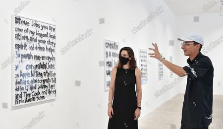 Italian artist Woc (R) explains one of his artwork to a visitor in the exibition 'Social Bloom' at Galleria Noir in Turin, Italy, 07 July 2020. The thirteen artworks are designed with spray whose subjects are seven tweets of US rapper Kanye West. Made on white wrapping paper with the spray technique, they are part of a larger artistic project that Woc dedicated a couple of years ago to West, the billionaire musician, stylist, record producer, also known for being Kim Kardashian's husband.