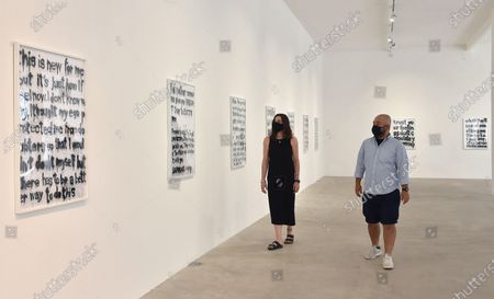 Visitors look at artworks by Italian artist Woc (24) in the exibition 'Social Bloom' at Galleria Noir in Turin, Italy, 07 July 2020. The thirteen artworks are designed with spray whose subjects are seven tweets of US rapper Kanye West. Made on white wrapping paper with the spray technique, they are part of a larger artistic project that Woc dedicated a couple of years ago to West, the billionaire musician, stylist, record producer, also known for being Kim Kardashian's husband.