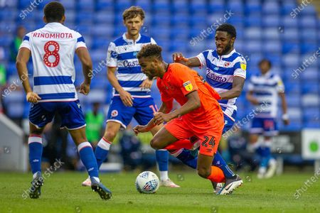 Stock Image of Huddersfield Town forward Steve Mounié (24) battles with Reading defender Tyler Blackett (24) during the EFL Sky Bet Championship match between Reading and Huddersfield Town at the Madejski Stadium, Reading