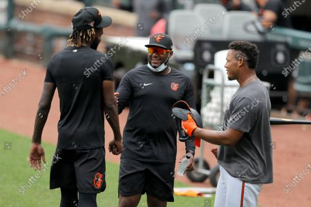 Baltimore Orioles second baseman Hanser Alberto, center, talks with relief pitcher Miguel Castro, left, and catcher Pedro Severino during baseball training camp, in Baltimore