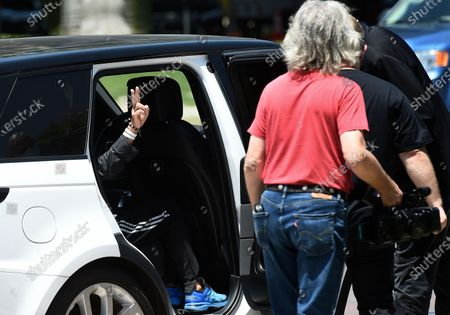 Musician Ringo Starr's hand gives the peace symbol as he enters a car to leave an event celebrating his 80th birthday, in Beverly Hills, Calif