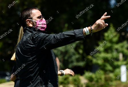 Musician Ringo Starr waves at onlookers at an event to celebrate his 80th birthday, in Beverly Hills, Calif