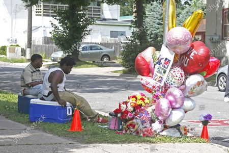 Two men sit at a memorial for a pregnant woman who was shot in south Minneapolis Sunday and died after being rushed to a hospital. Doctors at the Hennepin County Medical Center delivered the baby of the shooting victim who was in a vehicle when she was shot and later pronounced dead, according to authorities.The baby girl was placed in intensive care