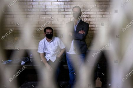 The sons of former Panamanian President Ricardo Martinelli, Ricardo Martinelli Linares, right, and his brother Luis Enrique wait inside a cell at the judicial court building in Guatemala City, . The brothers were detained on Monday on an international warrant from Interpol on charges of conspiracy to commit money laundering