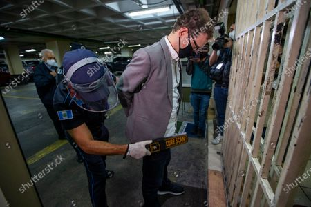 The son of former Panamanian President Ricardo Martinelli, Luis Enrique Martinelli Linares, is frisked by an officer before a hearing at the judicial court building in Guatemala City, . Luis Enrique and his brother Ricardo were detained on Monday by on international warrant from Interpol on charges of conspiracy to commit money laundering