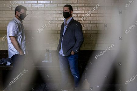 The sons of former Panamanian President Ricardo Martinelli, Ricardo Martinelli Linares, center, and his brother Luis Enrique stand inside a cell at the judicial court building in Guatemala City, . The brothers were detained Monday by on an international warrant from Interpol on charges of conspiracy to commit money laundering