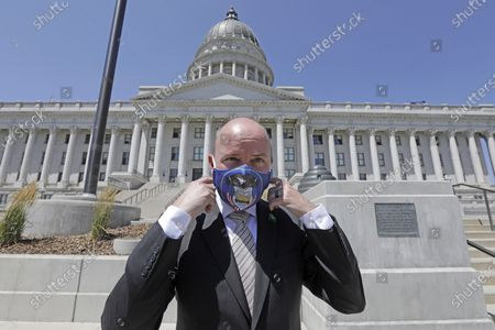 Lt. Gov Spencer Cox adjusts his face mask as he poses for a photograph at the Utah state Capitol, in Salt Lake City. Jon Huntsman Jr. was narrowly beaten Monday by Cox, who had heightened visibility as he helped respond to the coronavirus and managed to pitch himself as an earnest politician with rural Utah roots