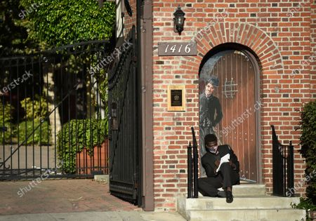 Stock Picture of Man sits in front of a drawing of Charlie Chaplin at the entrance to The Jim Henson Company, in the Hollywood section of Los Angeles