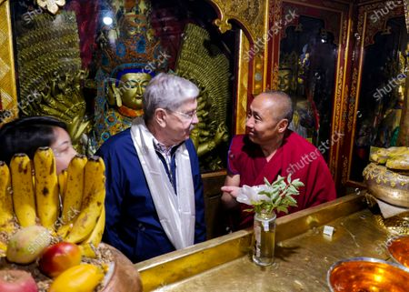 Taken May 23, 2019, and released by the U.S. Embassy in Beijing, U.S. Ambassador to China Terry Branstad, left, speaks with a monk at the Jokhang Temple in Lhasa in western China's Tibet Autonomous Region. China said, it will impose visa restrictions on U.S. individuals following the Trump administration's imposition of travel bans on Chinese officials it accuses of restricting foreigners' access to Tibet