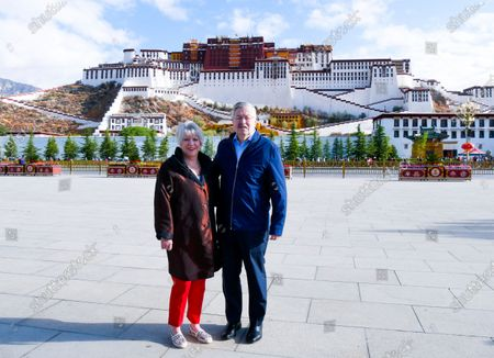 Taken May 22, 2019, and released by the U.S. Embassy in Beijing, U.S. Ambassador to China Terry Branstad and his wife Christine pose for a photo in front of the Potala Palace in Lhasa in western China's Tibet Autonomous Region. China said, it will impose visa restrictions on U.S. individuals following the Trump administration's imposition of travel bans on Chinese officials it accuses of restricting foreigners' access to Tibet