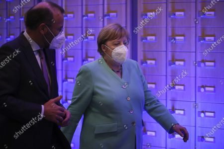 German Chancellor Angela Merkel, right, walks with MEP Manfred Weber, from Germany, as she leaves after addressing the plenary at the European Parliament in Brussels, . Germany has just taken over the European Union's rotating presidency, and must chaperone the 27-nation bloc through a period of deep crisis for the next six months and try to limit the economic damage inflicted by the coronavirus