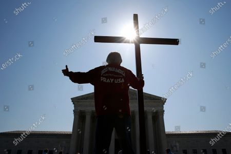 Tom Alexander holds a cross as he prays prior to rulings outside the Supreme Court on Capitol Hill in Washington, . The Supreme Court is siding with two Catholic schools in a ruling that underscores that certain employees of religious schools, hospitals and social service centers can't sue for employment discrimination