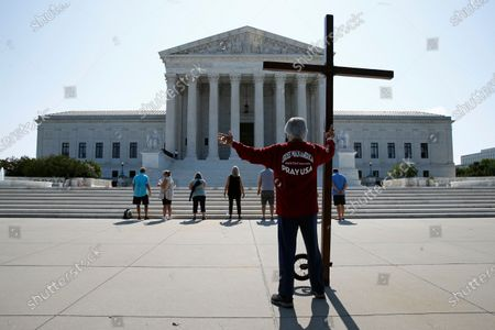Stock Picture of Tom Alexander holds a cross as he prays prior to rulings outside the Supreme Court on Capitol Hill in Washington, . The Supreme Court is siding with two Catholic schools in a ruling that underscores that certain employees of religious schools, hospitals and social service centers can't sue for employment discrimination