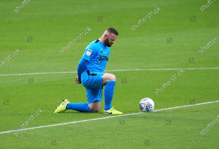Wayne Rooney of Derby County takes a knee ahead of the game