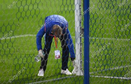 A member of the Sheffield Wednesday ground staff cleans and disinfects the goal post
