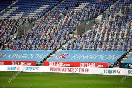 Cardboard cut outs of fans at thee DW stadium with EFL Screwfix LED advertising