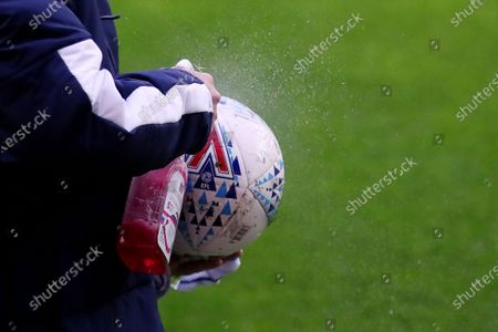 A match ball is sprayed with disinfectant