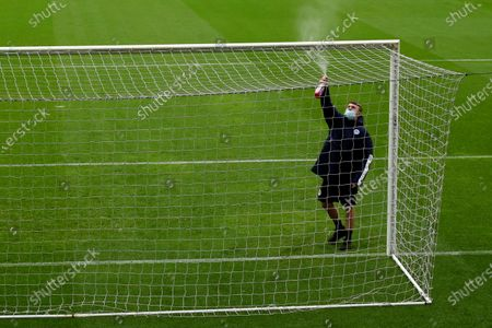 A groundsman sprays the goalposts with disinfectant prior to kick-off